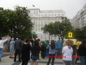 Manifestantes cantam o Hino Nacional perante a Banderia do Brasil hasteada no Copacabana Palace.